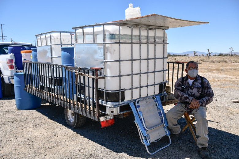 """José Huerta, a Lancaster resident, sits under his makeshift shade selling water containers in Lancaster, on July 2, 2021. The white containers sell for $100. """"A lot of people don't have water [in this city],"""" Huerta said. """"So people buy these water containers to store more water."""" Pablo Unzueta for CalMatters"""