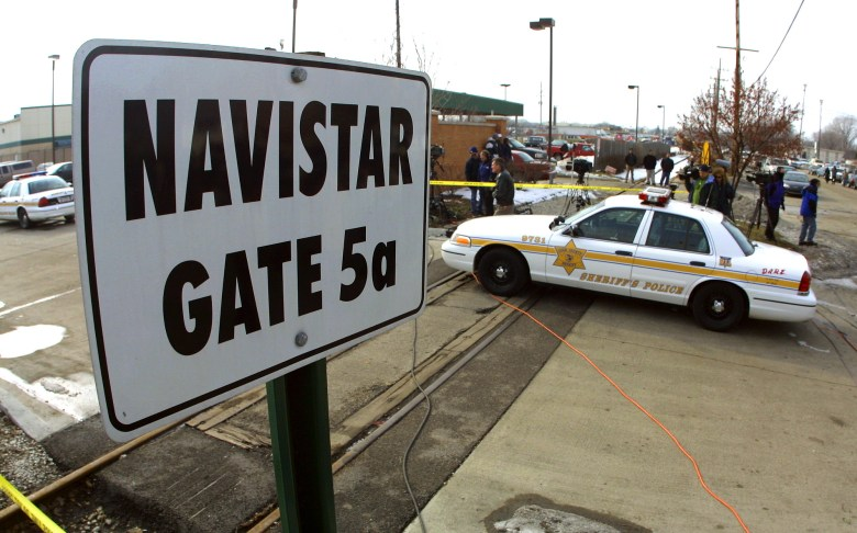 A police car guards an entrance to the Navistar International engine plant where authorities say a workplace shooting claimed five lives February 5, 2001 in Melrose Park, IL. A gunman believed to be a former employee killed five people including himself and injured at least four others after walking into the plant with an AK-47 assault rifle and opening fire. Photo by Tim Boyle, Newsmakers via Getty Images