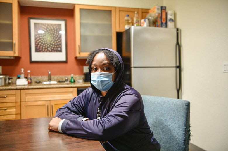 """Rasheena McCord sits on the kitchen table inside a hotel in Long Beach, on July 26, 2021. McCord has been living in hotels with her kids for one year after getting evicted. While McCord was at work, Los Angeles County sheriff's deputies came to the apartment to evict the family. """"We've been in hotels ever since."""" Photo by Pablo Unzueta for CalMatters"""